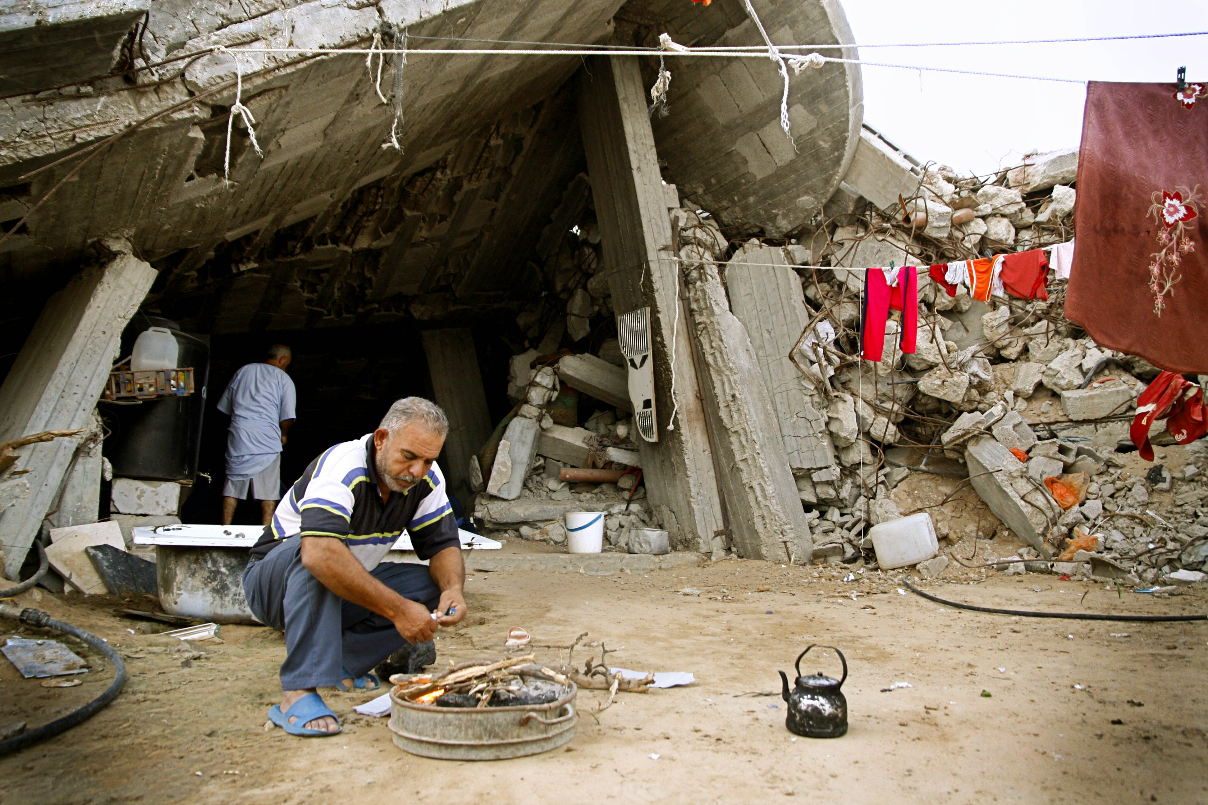 Man in Gaza steekt vuur aan voor de thee voor de resten van zijn aan puin geschoten huis.